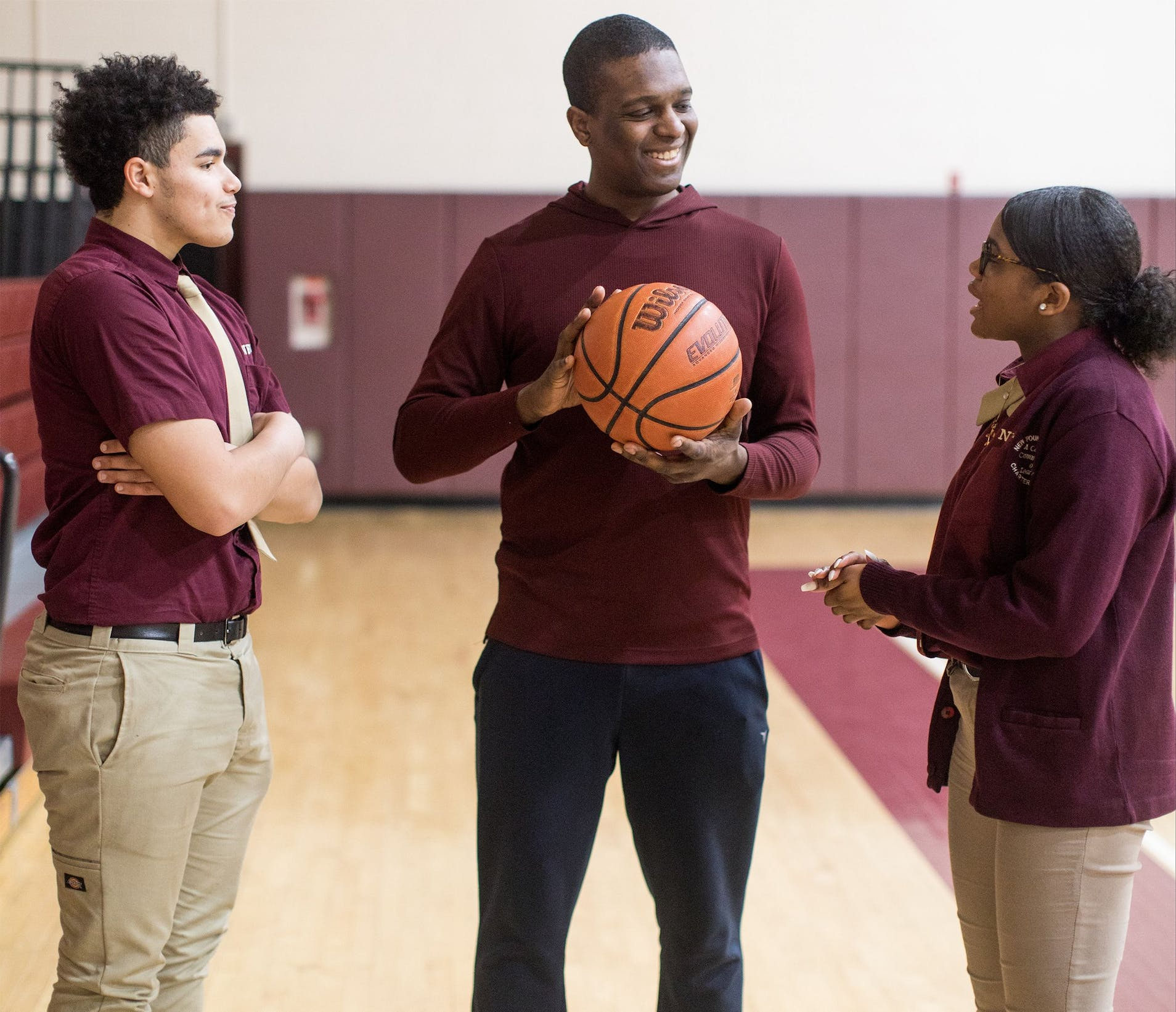 Three high school students chatting with a basketball