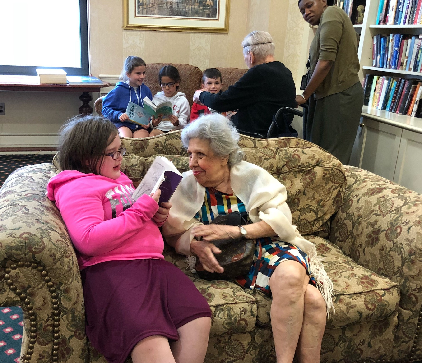 Young female student reads a book to a female senior citizen