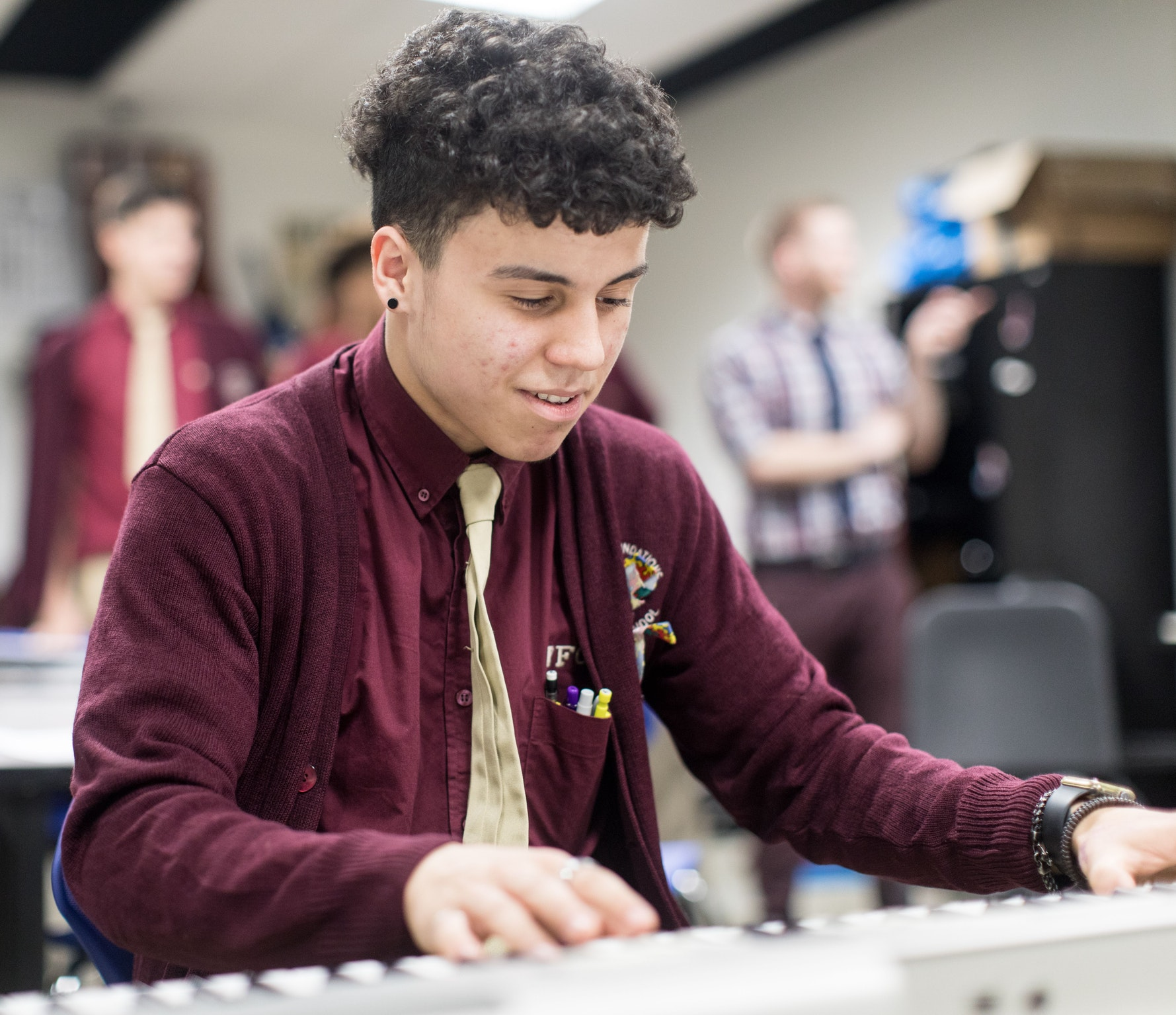 Male high school student plays electric keyboard in music class