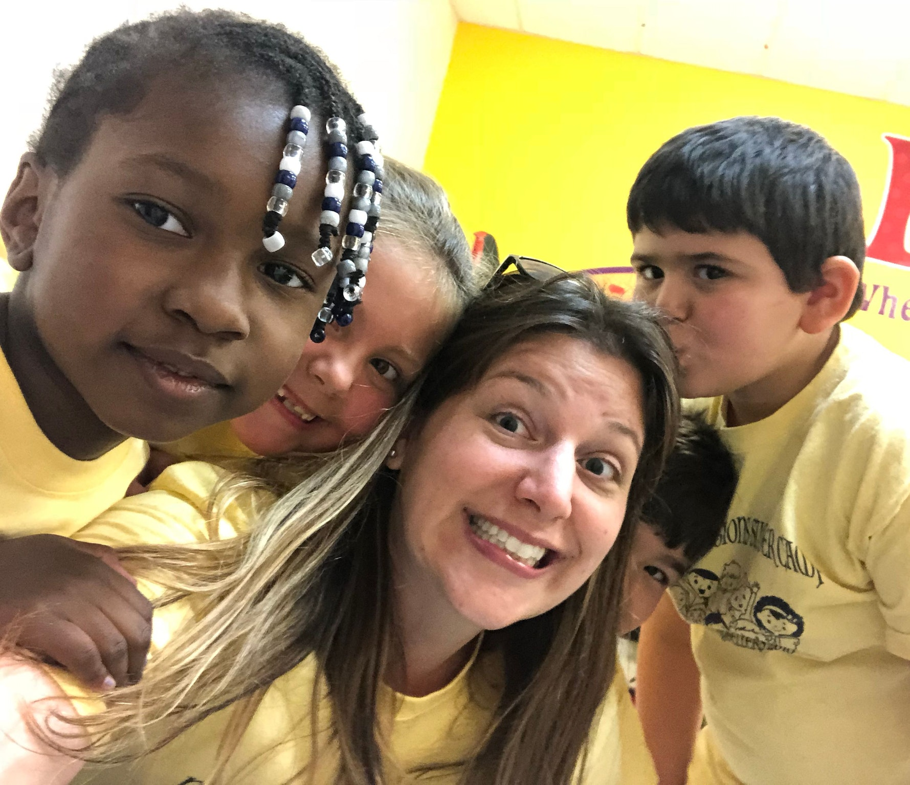Tiffany Searles smiling while surrounded by young students in yellow shirts