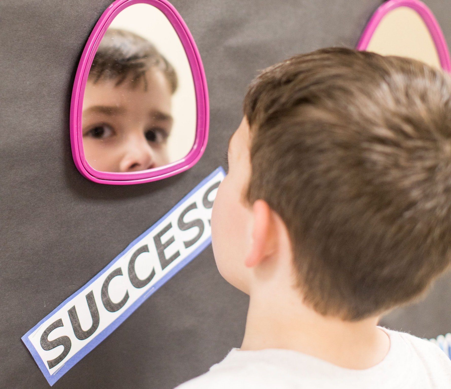 Young male student looks at camera through mirror reflection