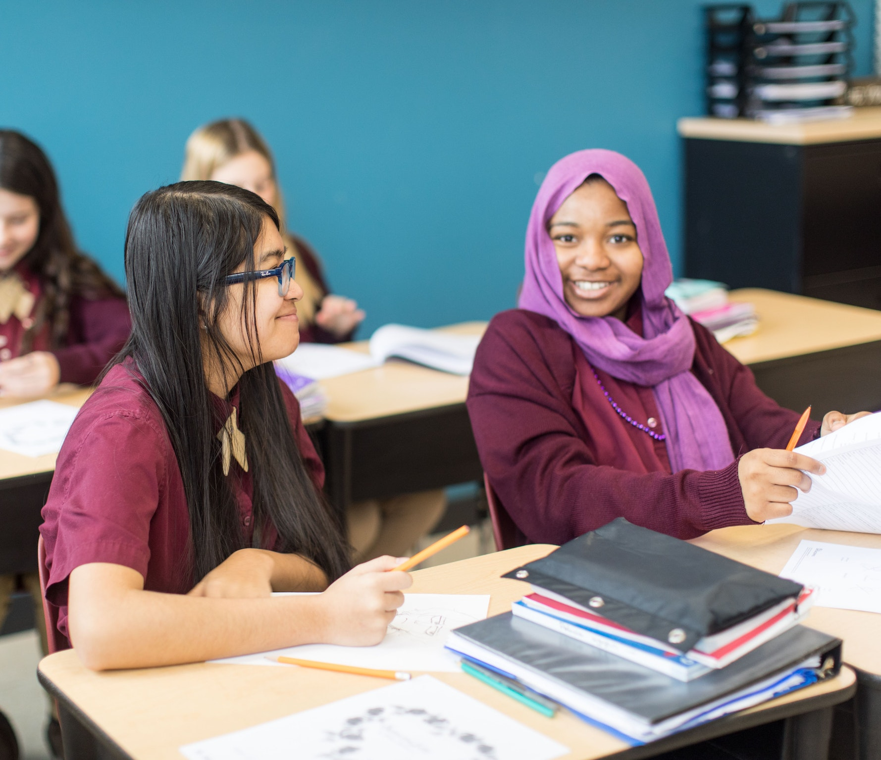 Two young female students smile while seated at their desks in class