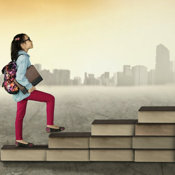 Girl climbing up stairs made of books