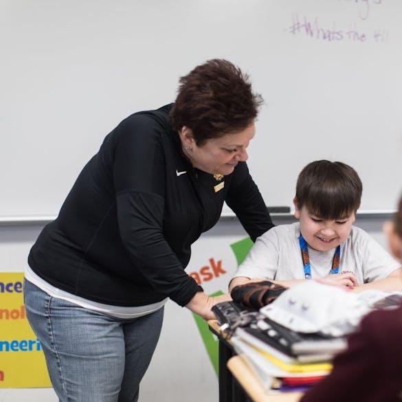 Teacher looking over student's shoulder at his work