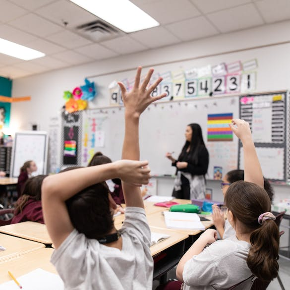Young students raising their hand in class