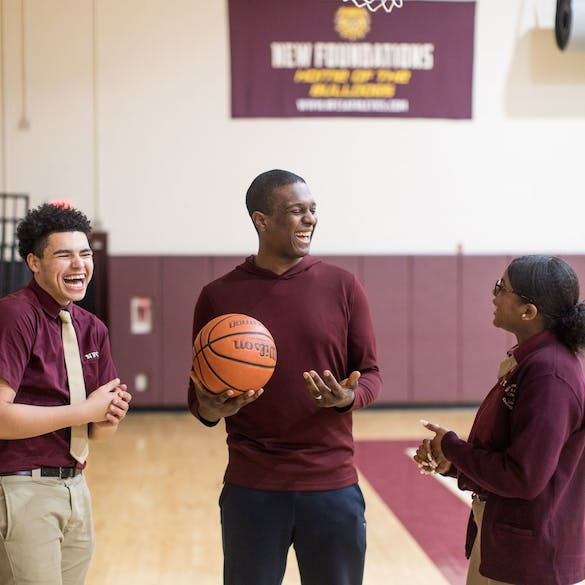 Senior students laughing with a basketball in the gym