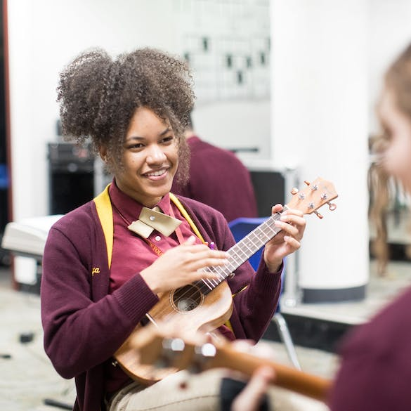 Two young female students play stringed instruments in music class