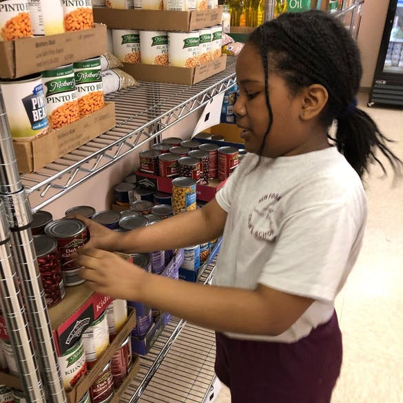 Young female student stacks canned foods on a shelf