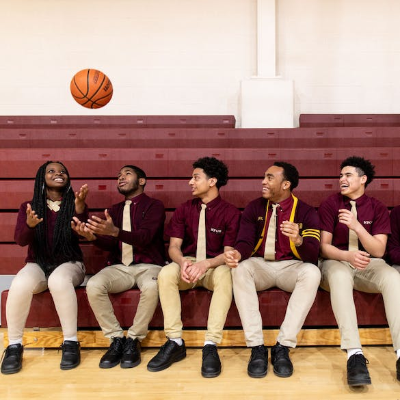 Five teenage students laughing in gym with basketball