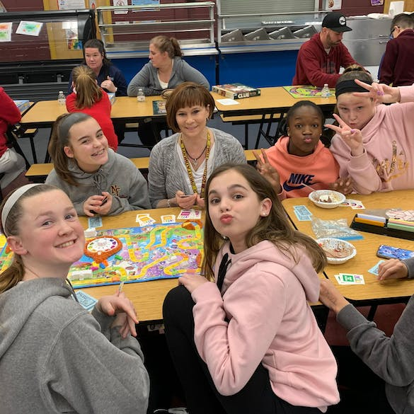 Six young female students smiling while playing board games