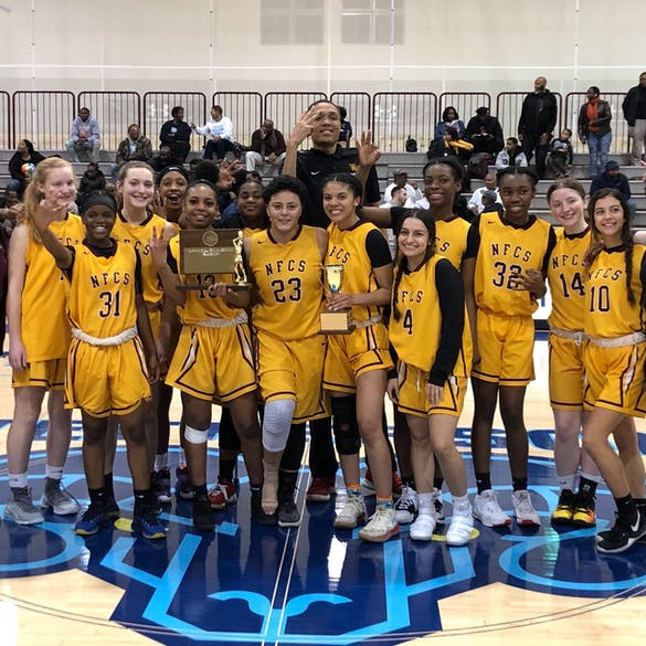 Female basketball team posing with trophies