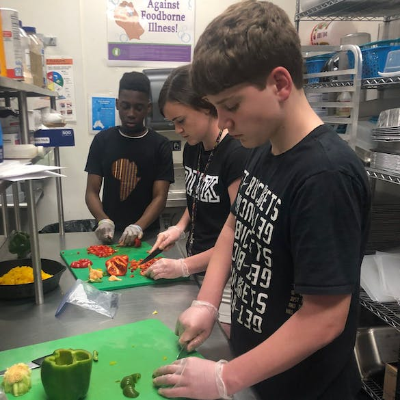 Three students chopping vegetables