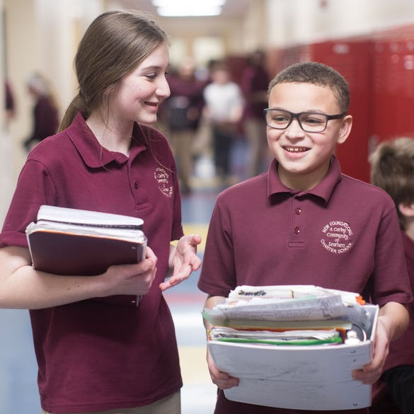 Young male and female student laughing while carrying binders in school hallway