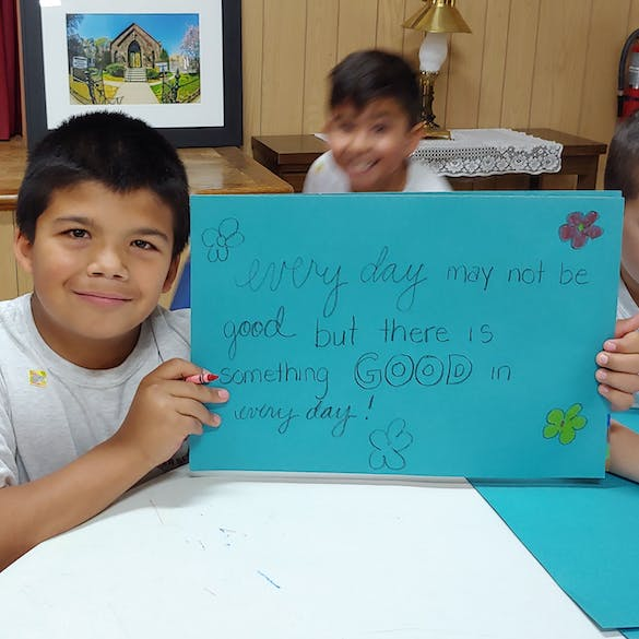 Young male student smiling and holding sign that says every day may not be good, but there is something good in every day