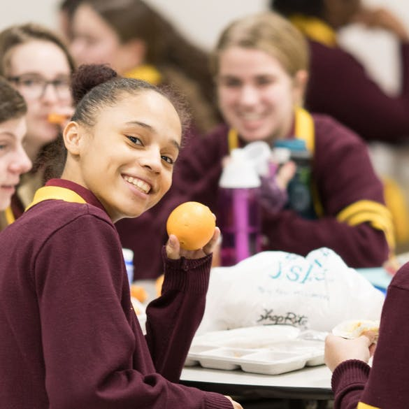 Young female student smiling while holding up an orange in the lunch room