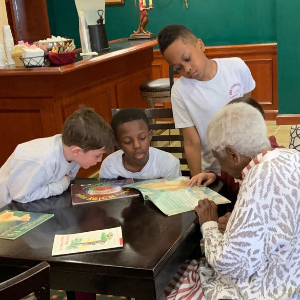 Three young male students reading a book with a senior citizen