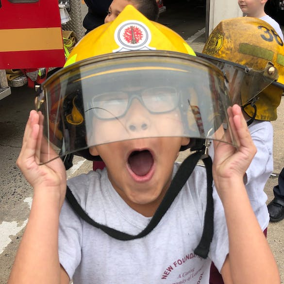 A young male student makes a silly face from under a fire fighter's helmet.
