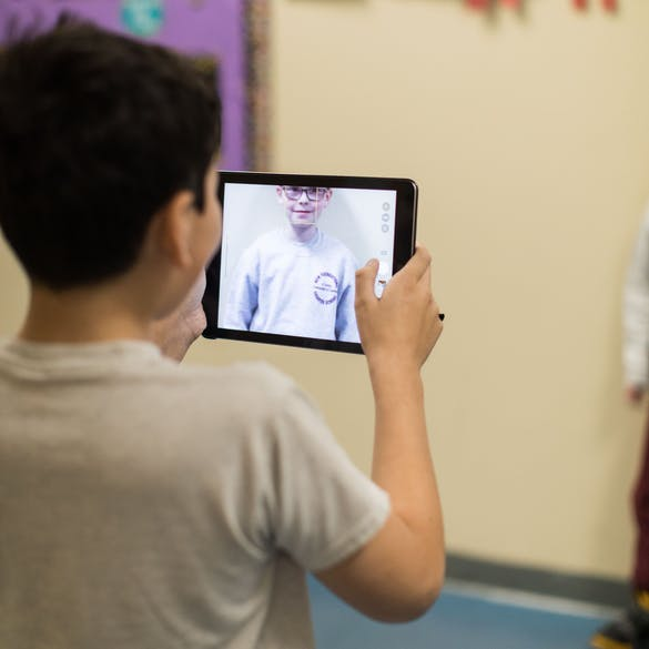 Young male student photographing another student with a tablet