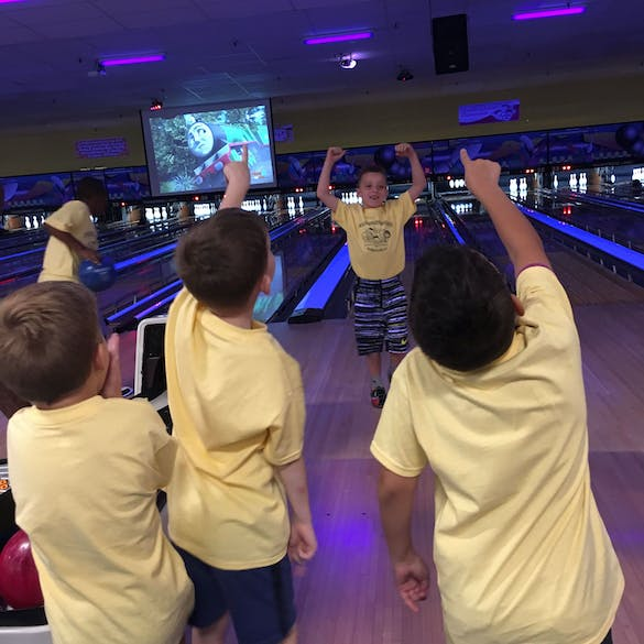 Young male students cheer on a classmate while bowling