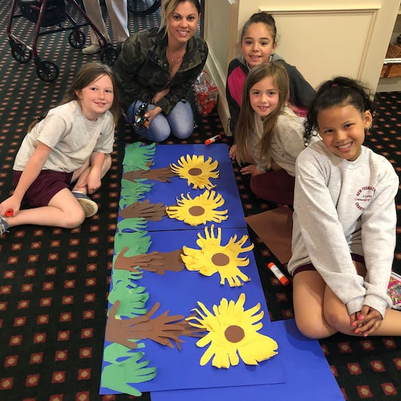 4 young female students and a female teacher pose around artwork of sunflowers