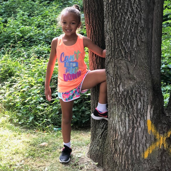 Young female student poses outdoors with a large tree