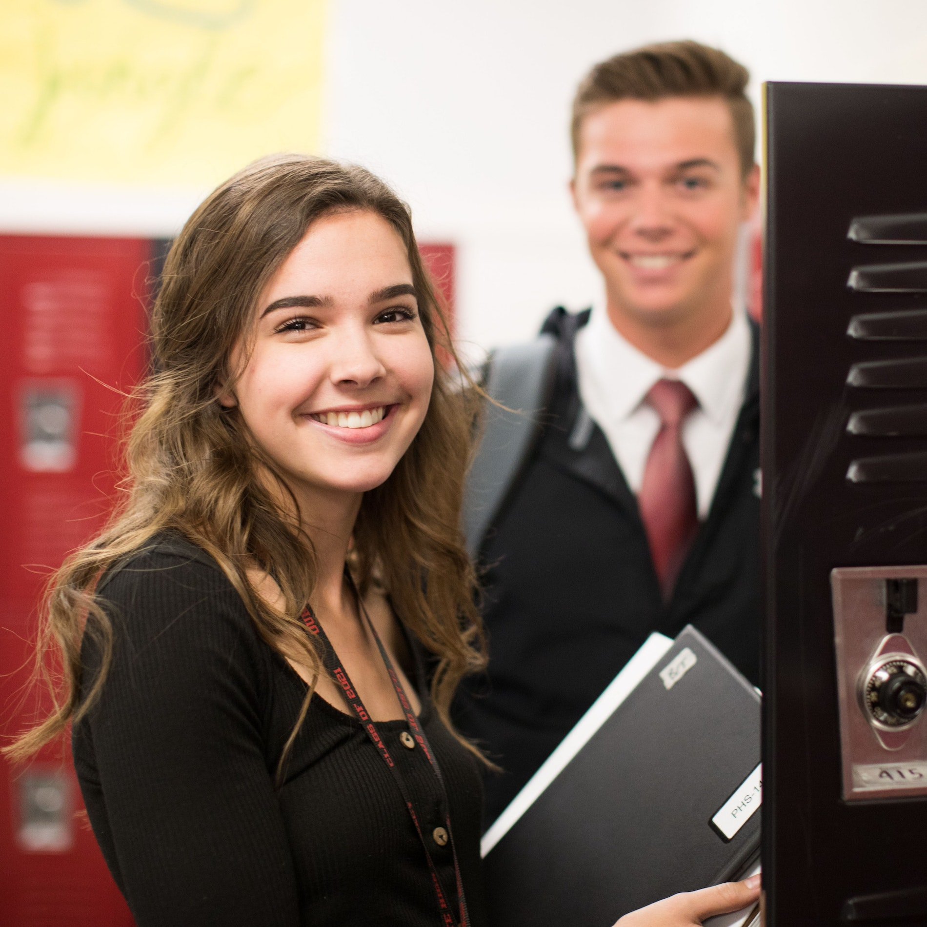 A female and a male student smiling by lockers.