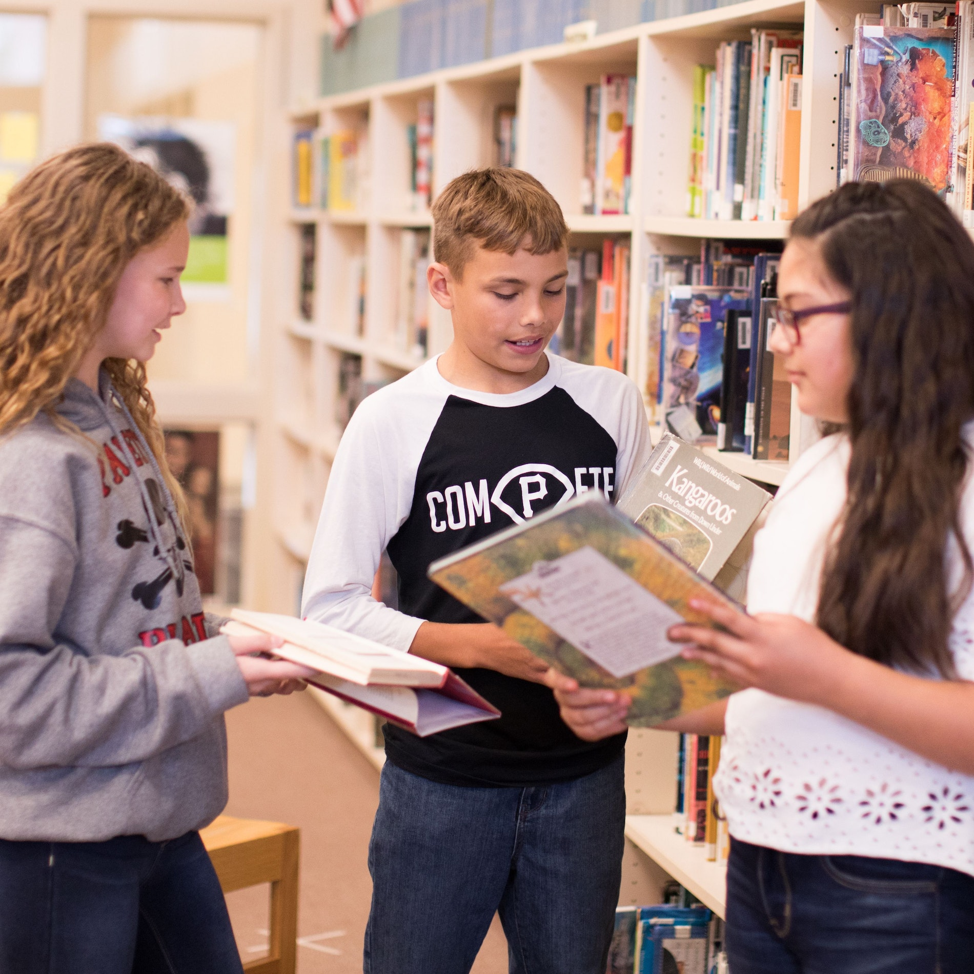 Three students sharing books in the library.
