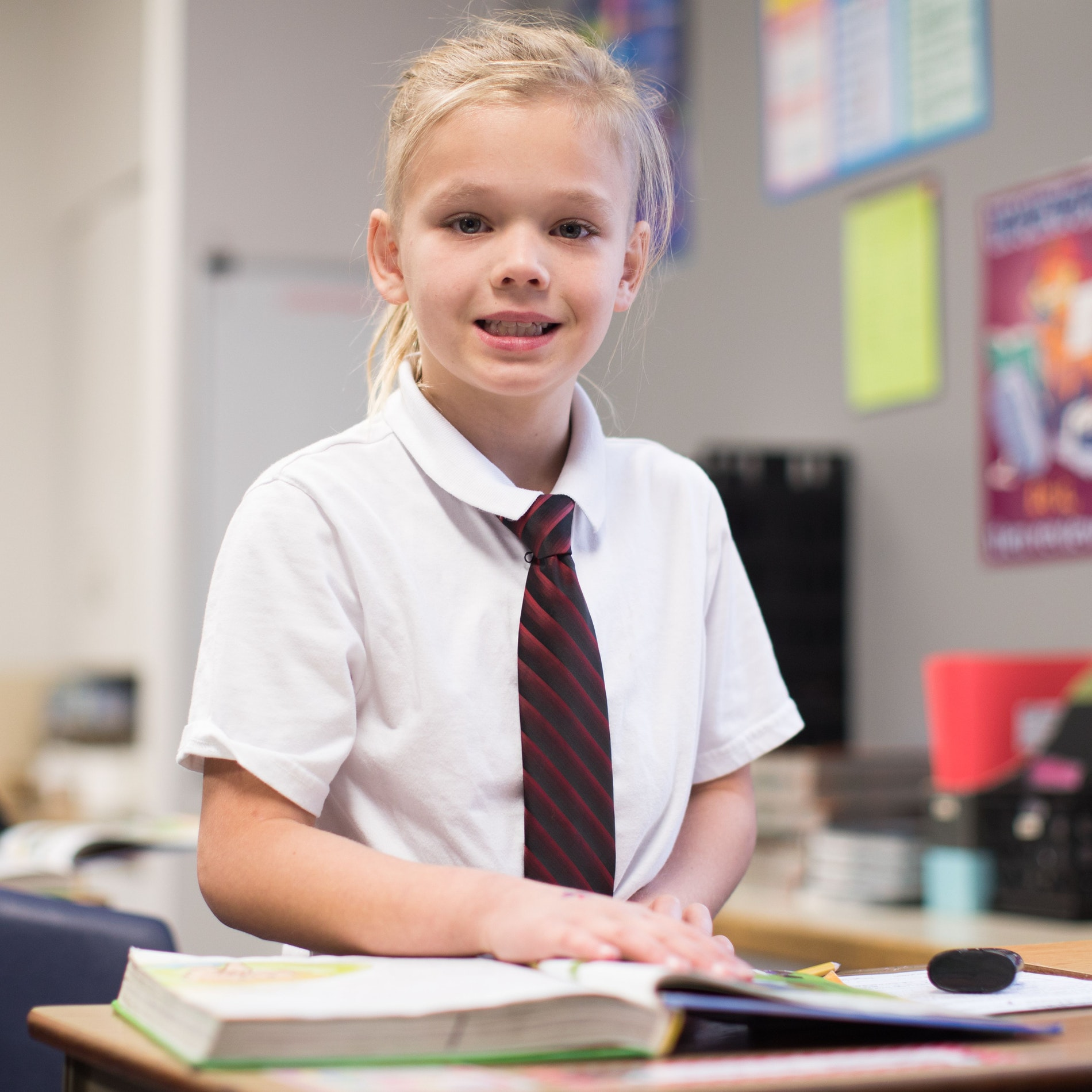 Girl smiling with textbook open on desk .