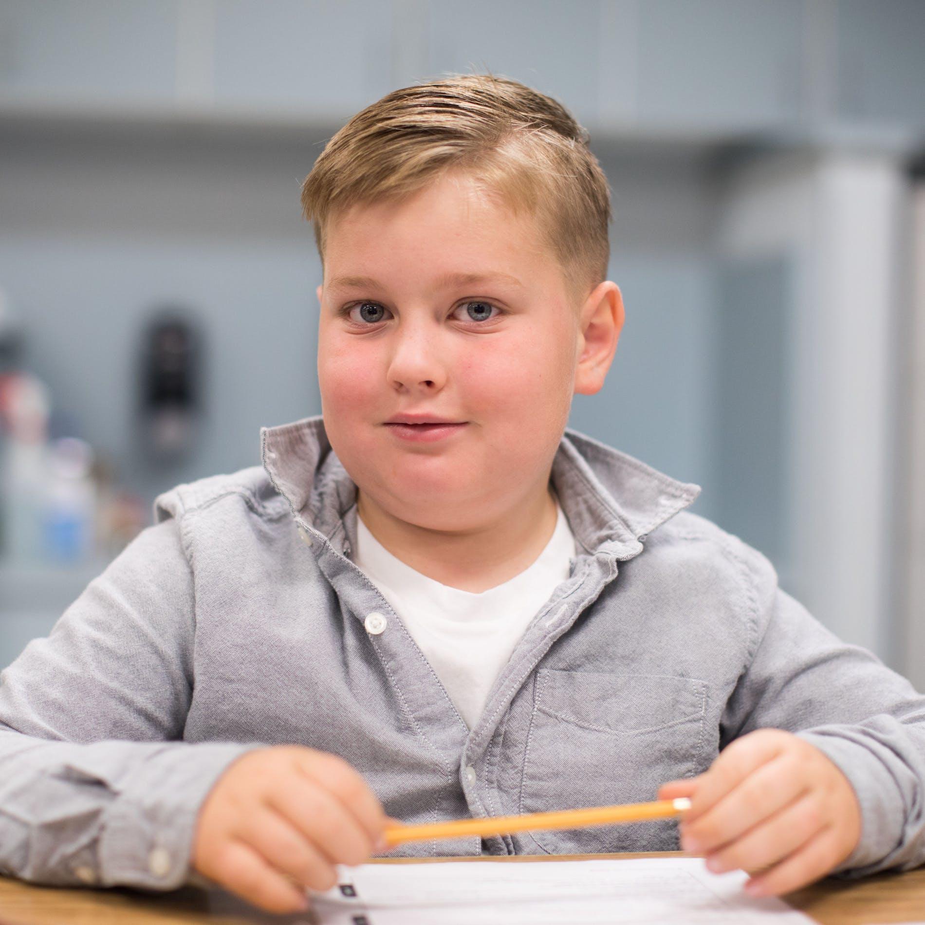 Pensive boy holding pencil.