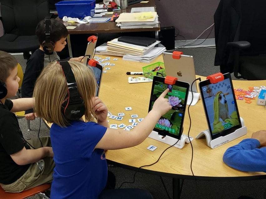 Girl with headphones working on Osmos and iPad.