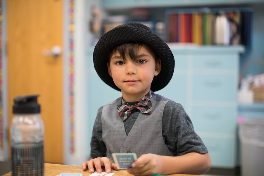 Boy wearing hat working with cards at desk.