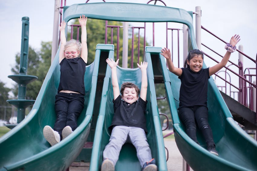 Three students sliding down a triple slide with arms in the air.