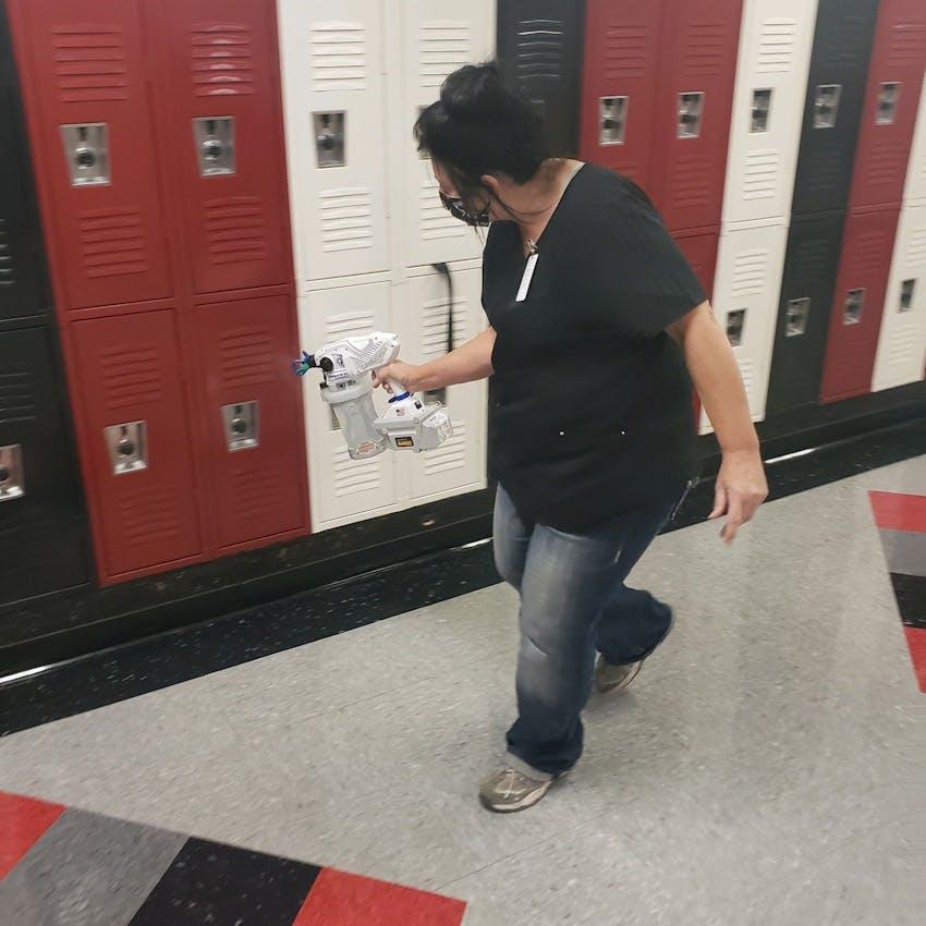 Female custodian wearing mask and spraying sanitizer on lockers in hallway.