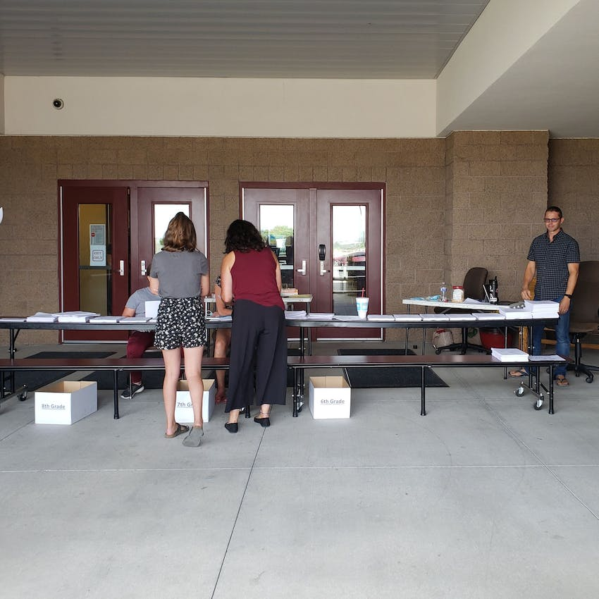 Outdoor school registration with tables and staff helping parents.