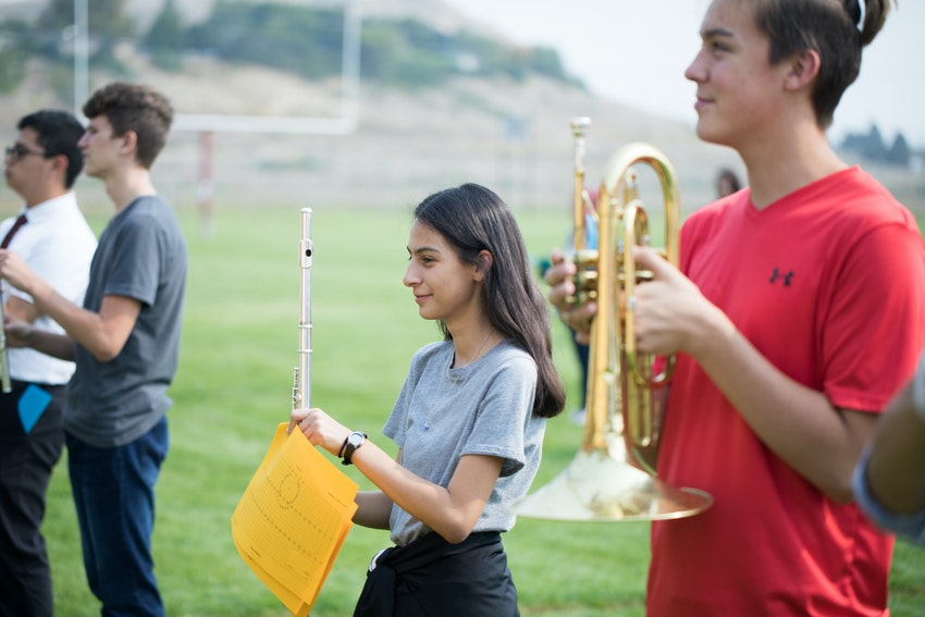 Marching band practice with two female students.