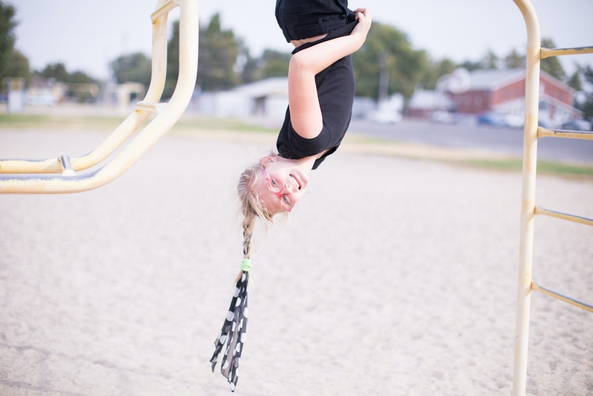 Girl hanging upside down from monkey bars.