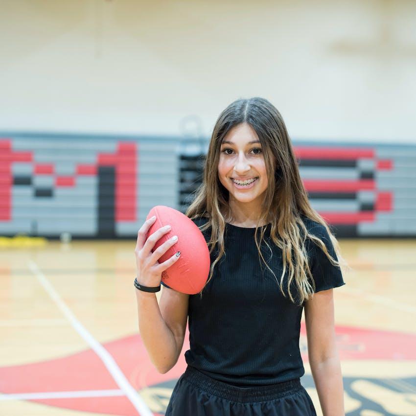 Smiling female athlete holding football.