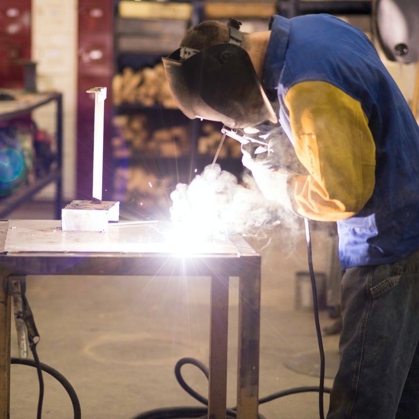 Male student welding.