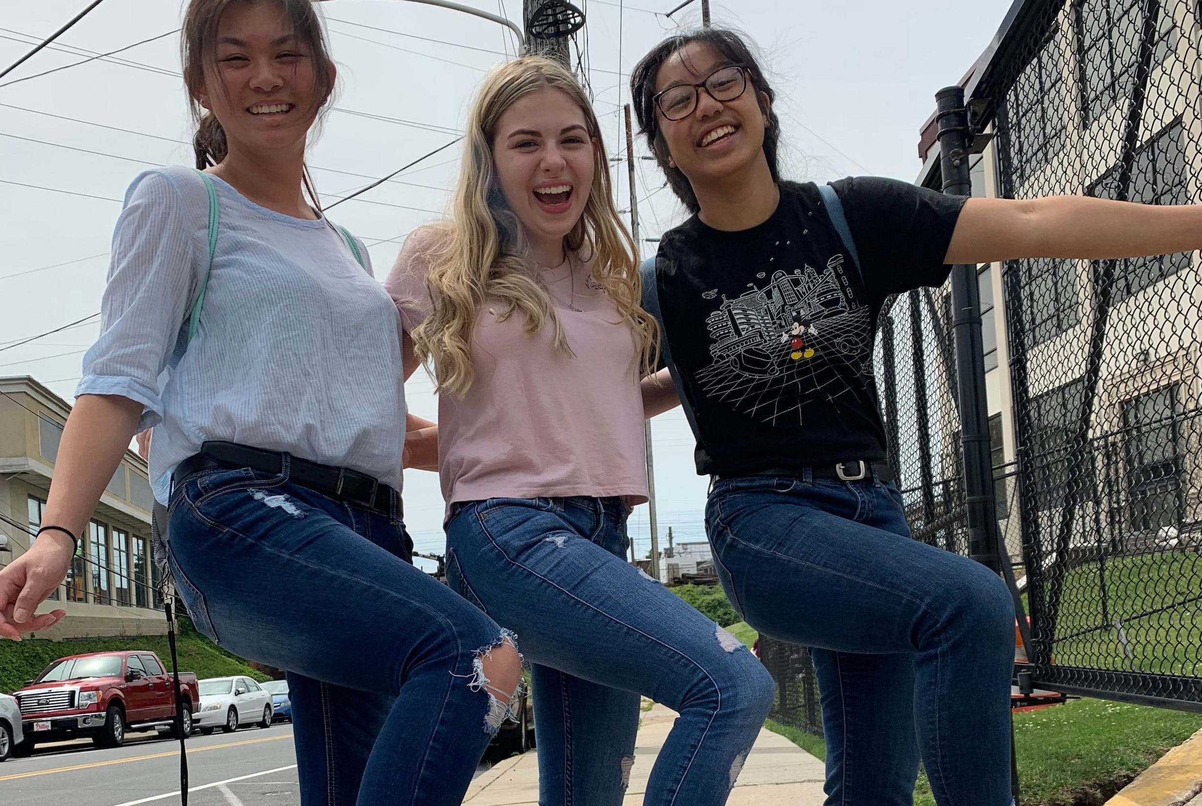 Three female students walking in tandem while laughing