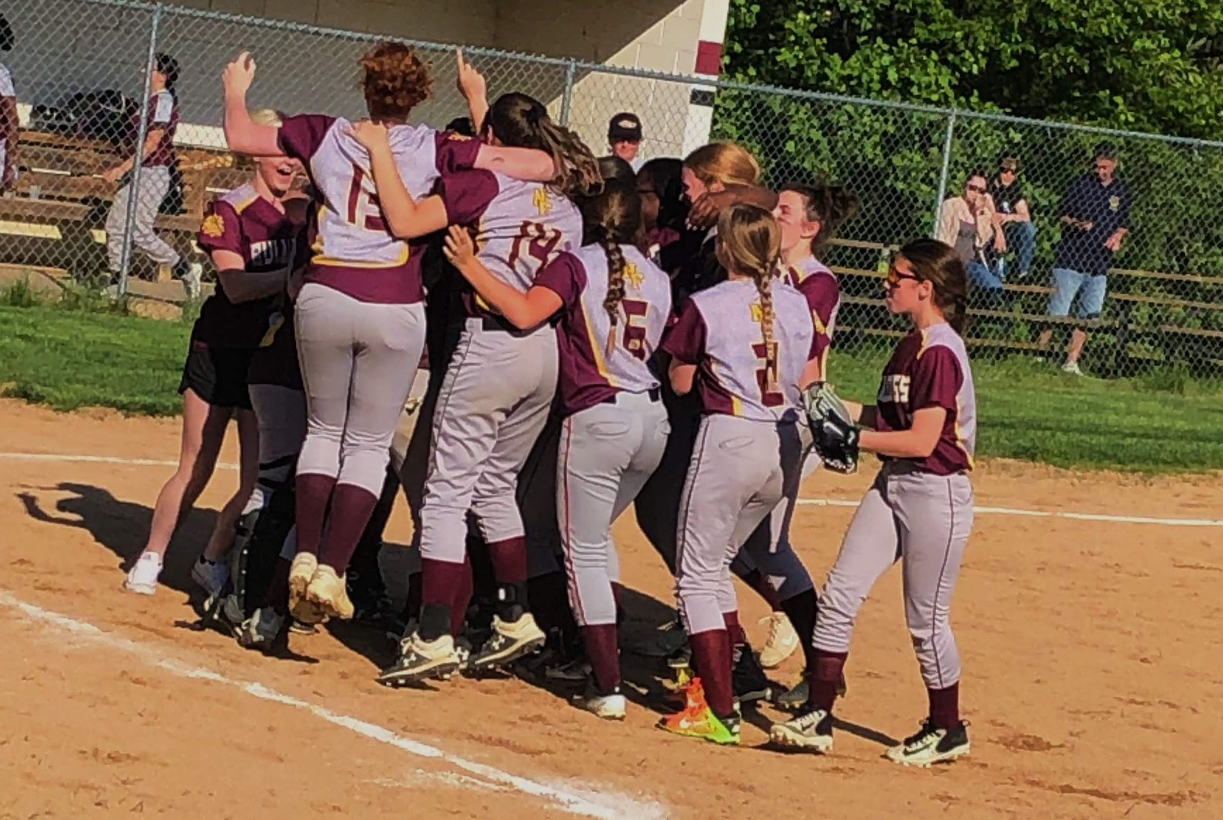 Girls softball team celebrating in a huddle on the playing field
