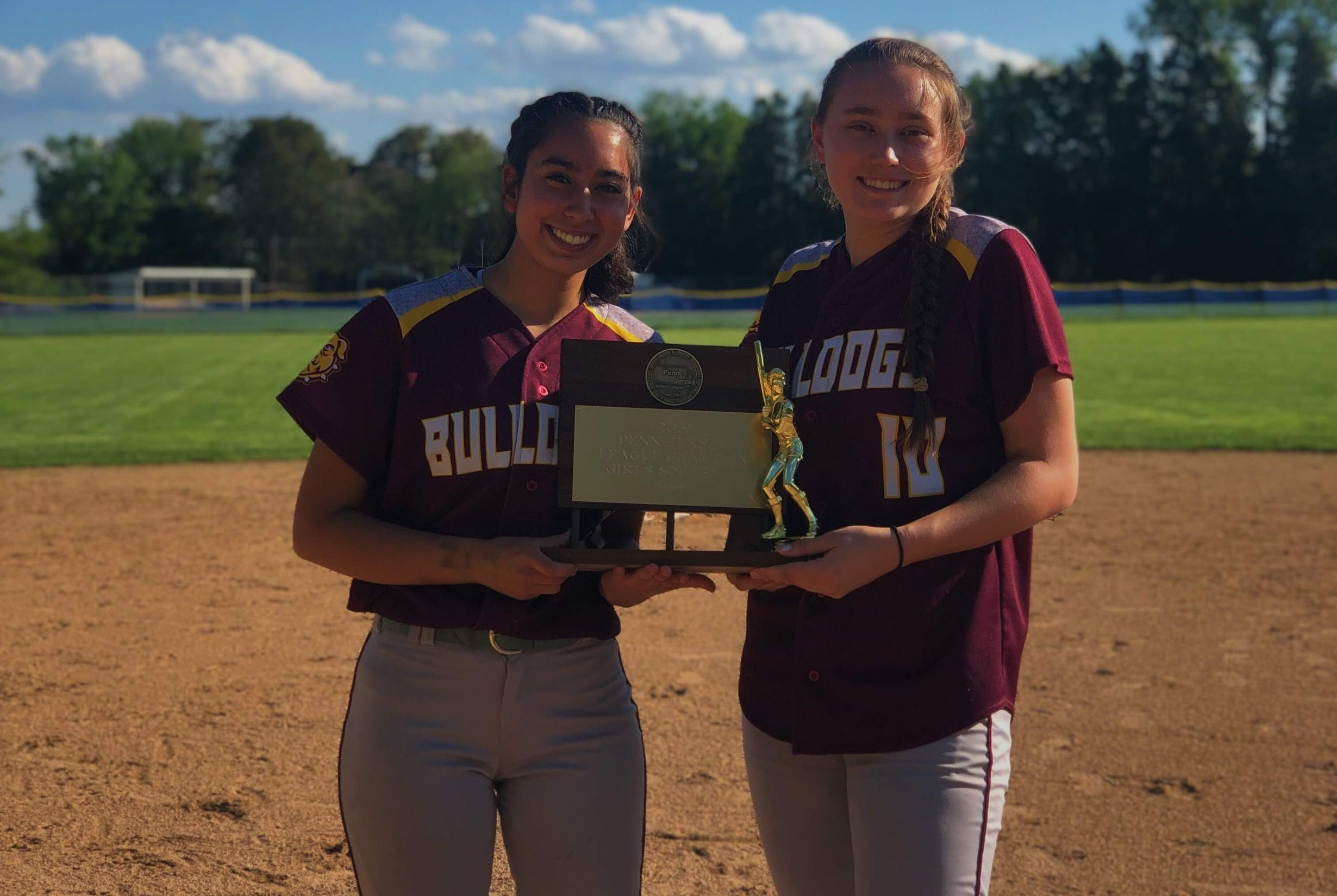 Two female softball players smiling while holding up trophies on the playing field