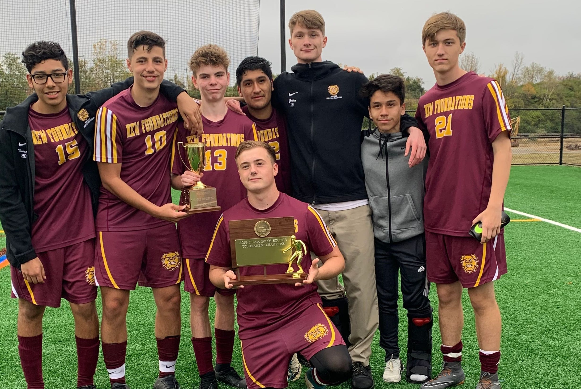School soccer team poses on the playing field with trophies