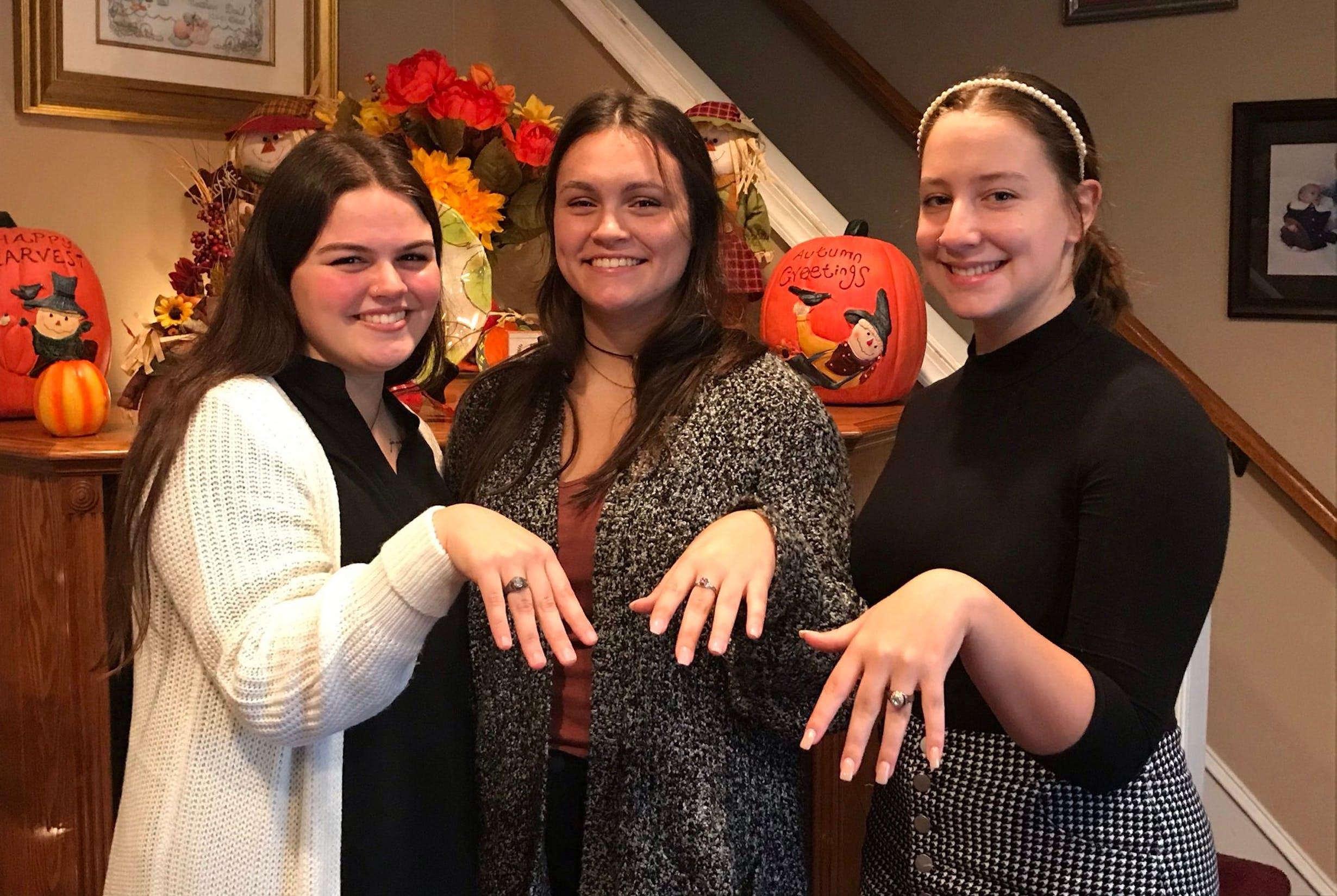 Three female students pose with their new class rings