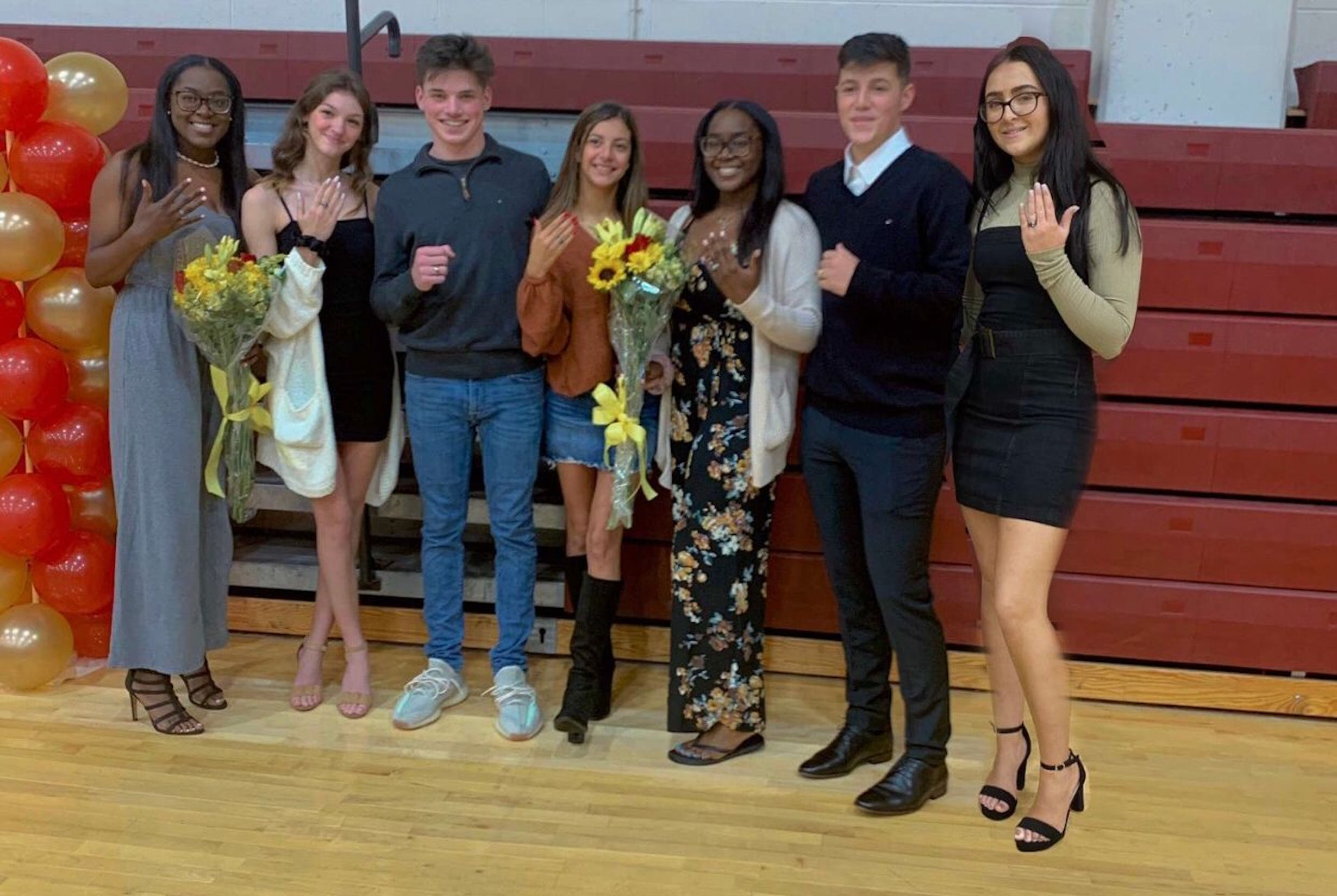 A group of male and female students pose with their new class rings in the school gym
