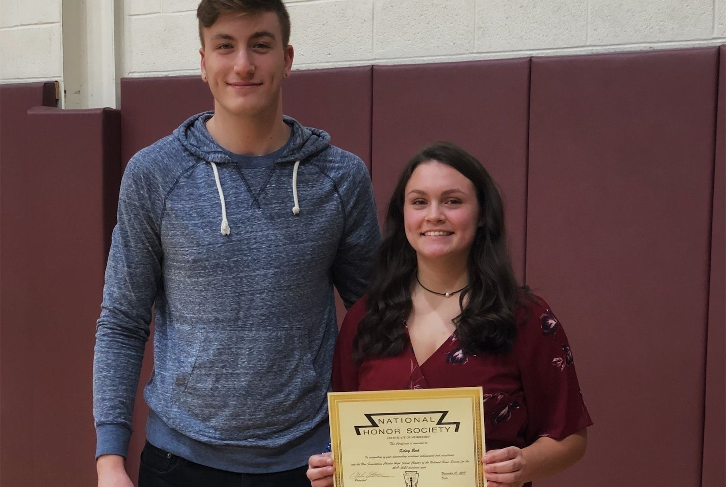 A male and female student smile while holding up a certificate