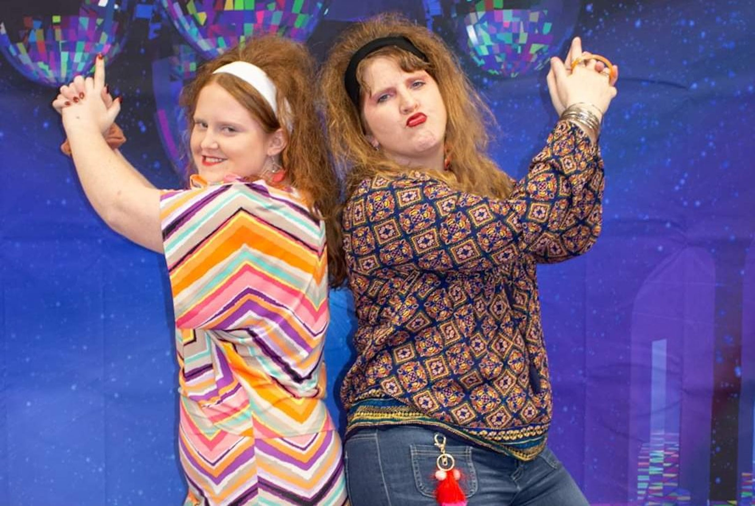 Two female students perform a Charlie's Angels pose at a school 70's themed dance