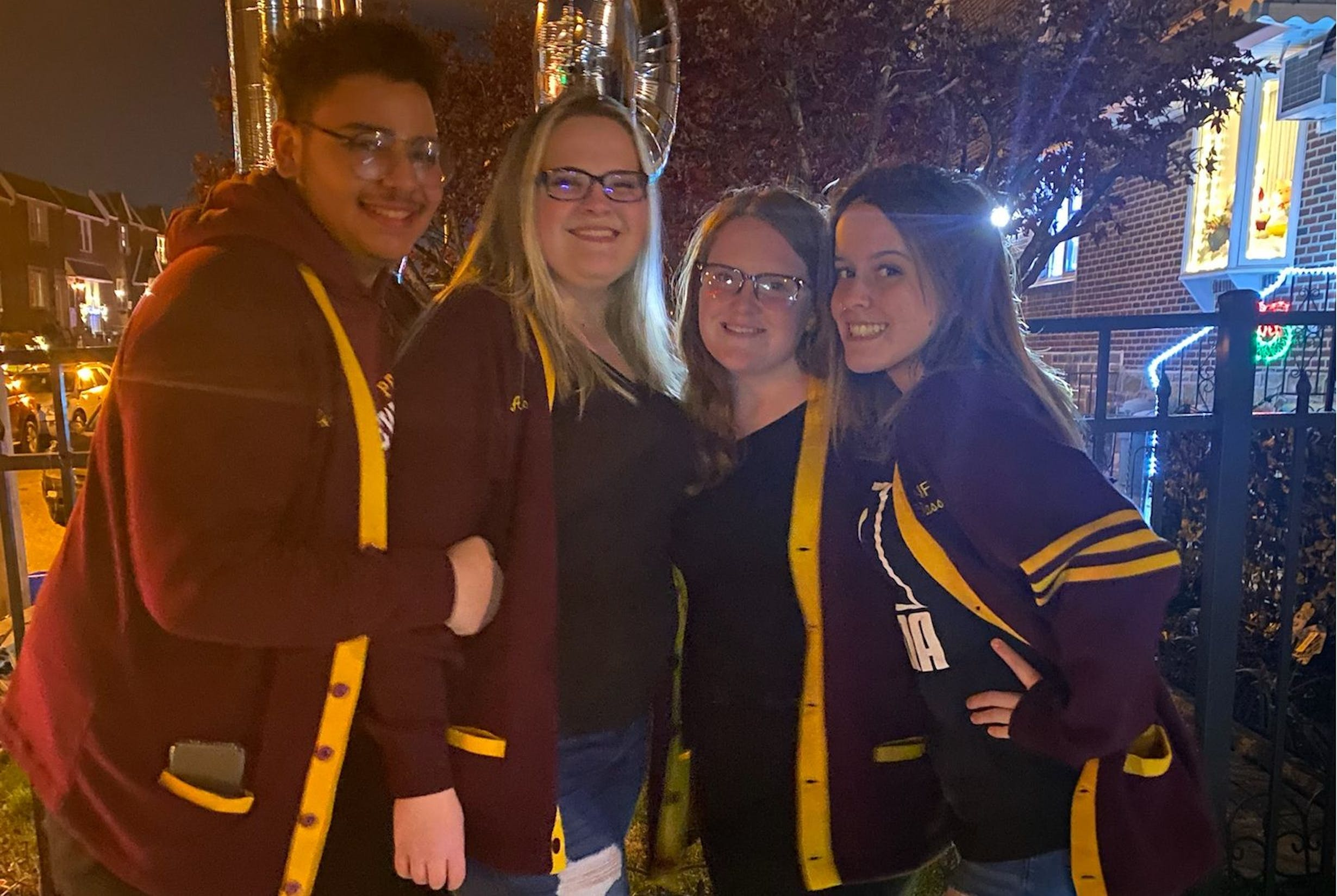 Four students pose outside in the evening wearing their senior New Foundations sweaters