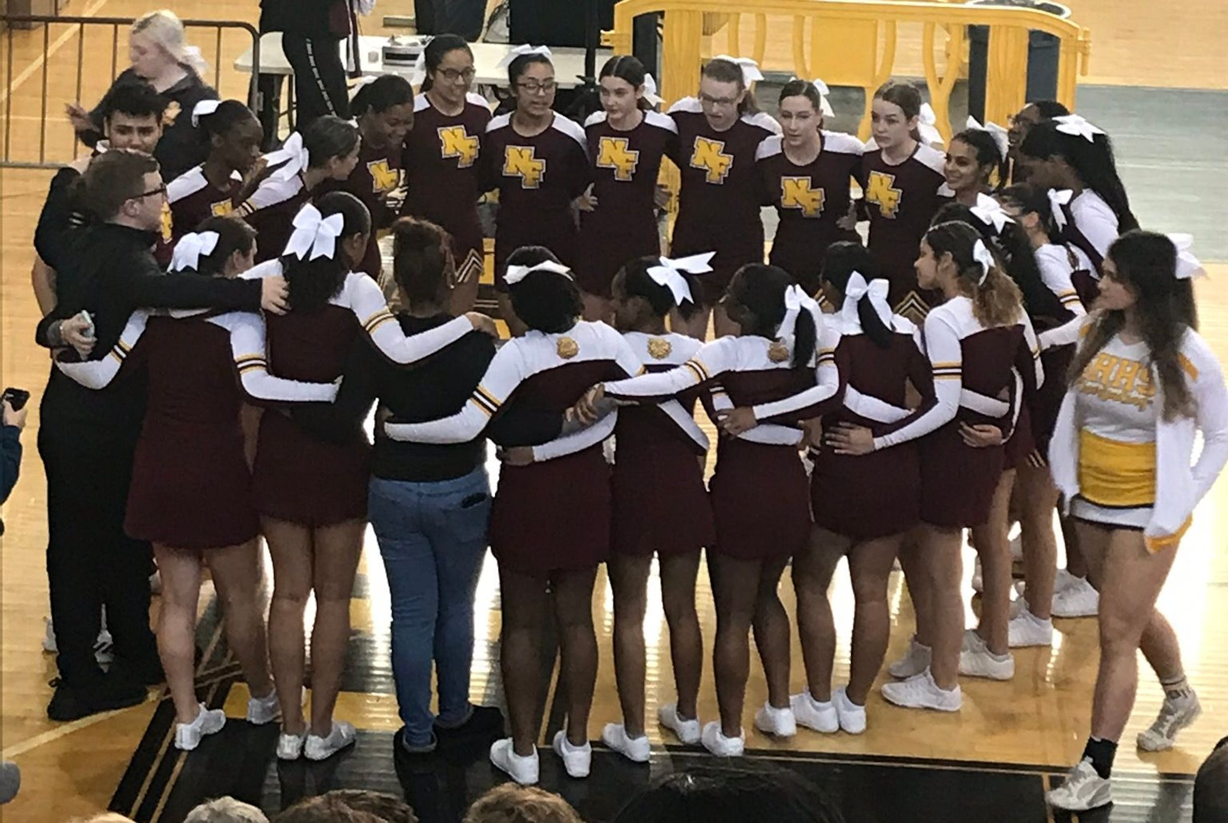 Group of cheerleaders huddled before a game in the school gym