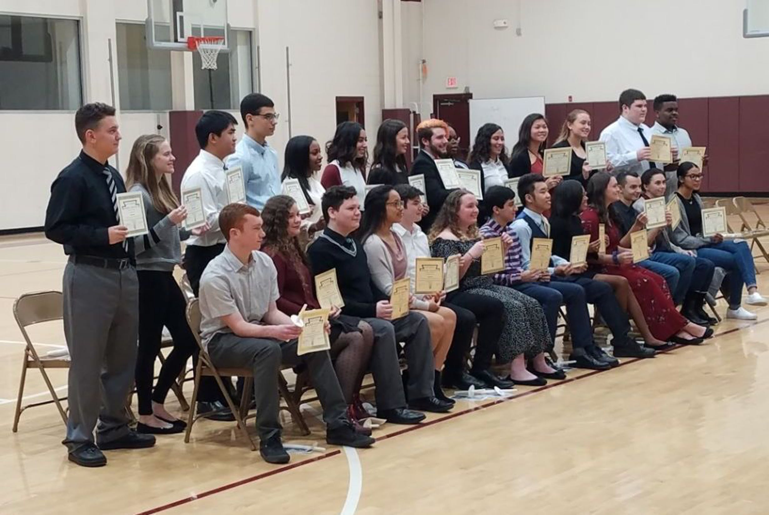 Large group of students sitting while holding up certificates in the school gym