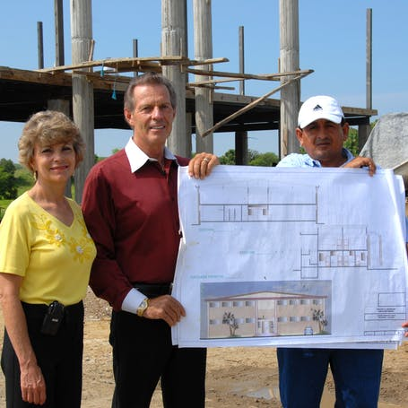 Young Living Foundation - Our Story - Gary and Mary Young holding blueprints of the Young Living Academy